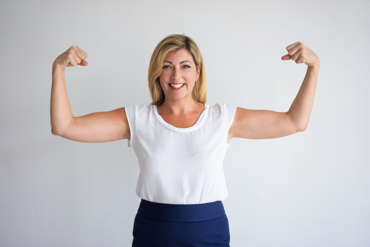 Happy Mature Caucasian Woman Flexing Biceps, wondering about menopause.