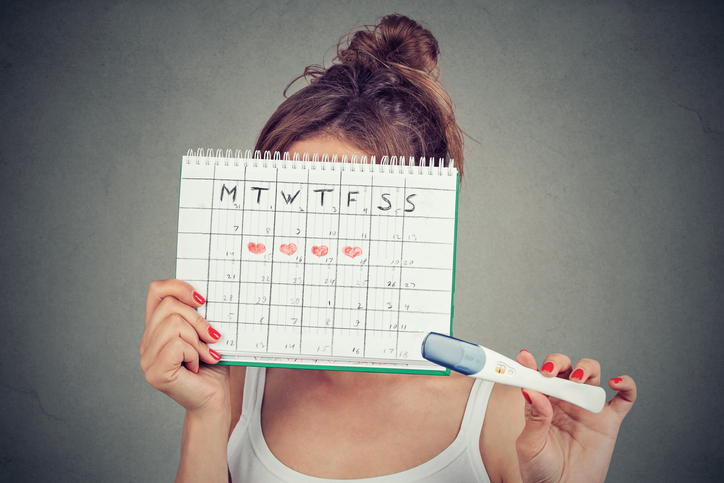 Young woman hiding behind a periods calendar and showing a positive pregnancy test, successfully knowing how to tell when you're ovulating