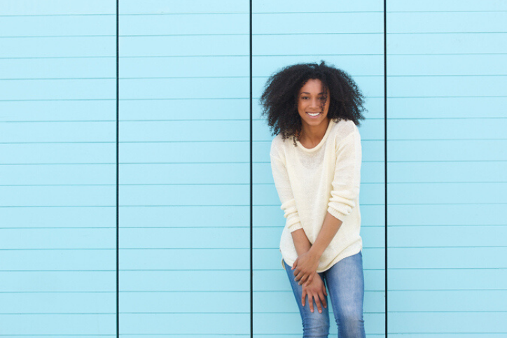 Young woman smiling on blue background