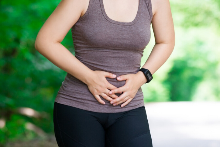 Woman with Endometriosis pain holding her stomach in a park.