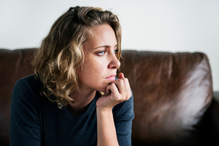 young Caucasian woman sitting on leather sofa worried about irregular menstrual bleeding.