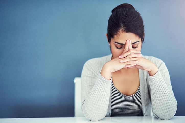 Woman leaning into her hands, looking stressed out, wondering about how stress impacts your period.