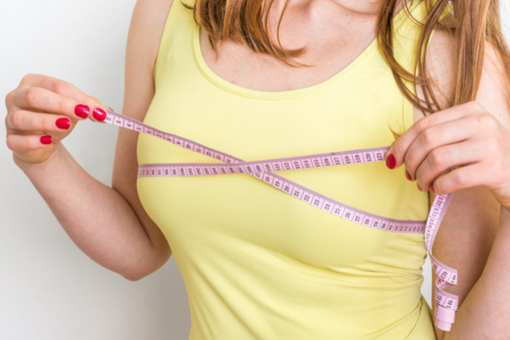 A woman wearing a yellow tank top with tap measure around her breasts, trying to figure out the right bra size for you.