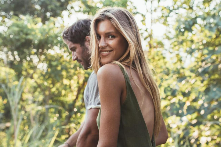 Blond woman walking with her brown haired boyfriend, wondering about health conditions that are related to reproductive health.