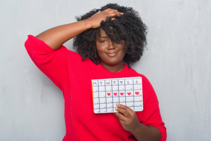 Black woman confused about when to see a doctor about abnormal menstrual cycles.