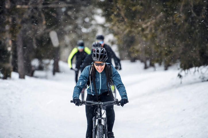 A group of young mountain bikers riding on road outdoors in winter, staying active this winter.