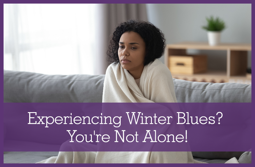 African American woman sitting on couch wrapped up in blanket, experiencing winter blues.