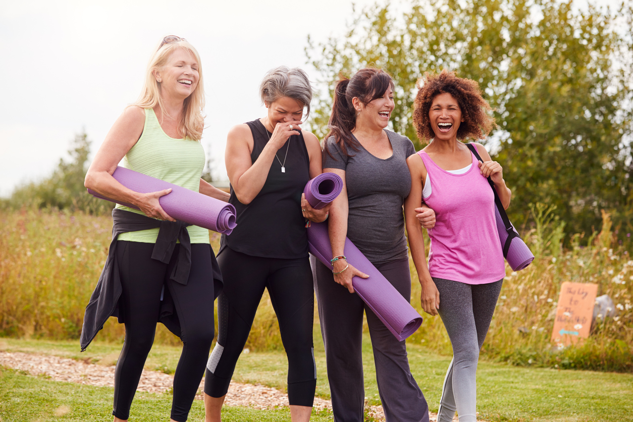Group Of Mature Female Friends On Outdoor Yoga Retreat Walking Along Path Through Campsite, discussing Most Common Health Issues Women Face in Their 40s.