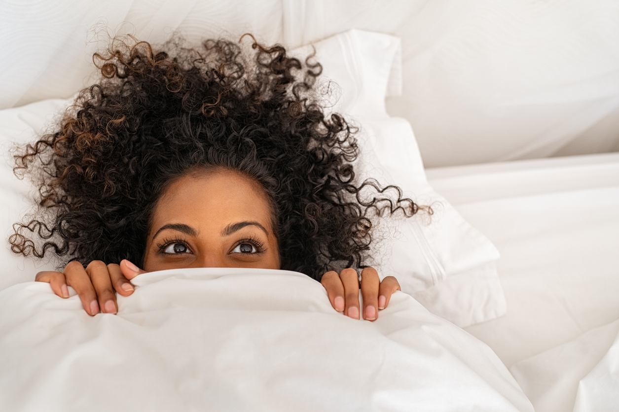 Funny young woman lying in bed and hiding under sheet while looking up with copy space. Top view of african american girl hiding face under white blanket on bed in the morning. Close up portrait of beautiful woman with curly hair covering face with bed sheet, wondering the the health impacts of orgasms.