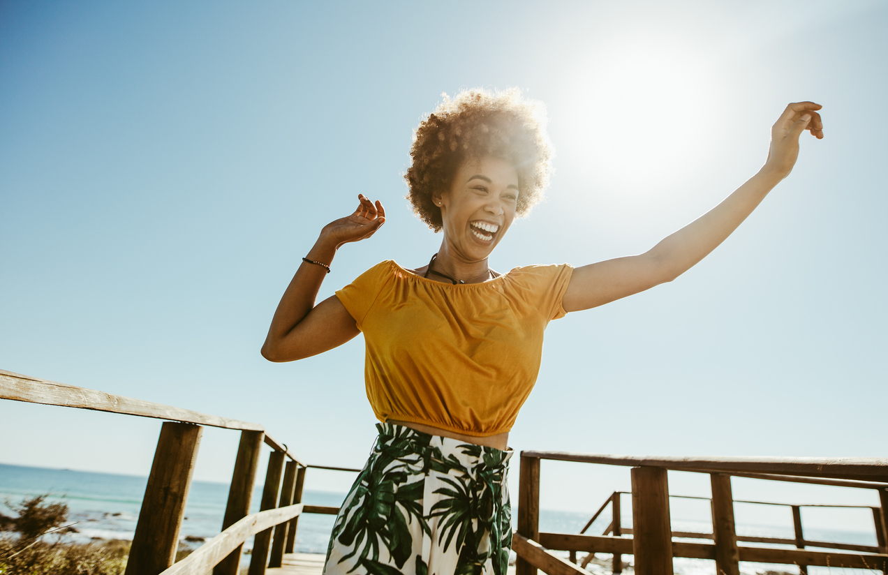 Excited young woman running on a boardwalk with her hands raised on a sunny day. African female having fun on summer vacation at the seaside, knowing how your happiness can impact your health.