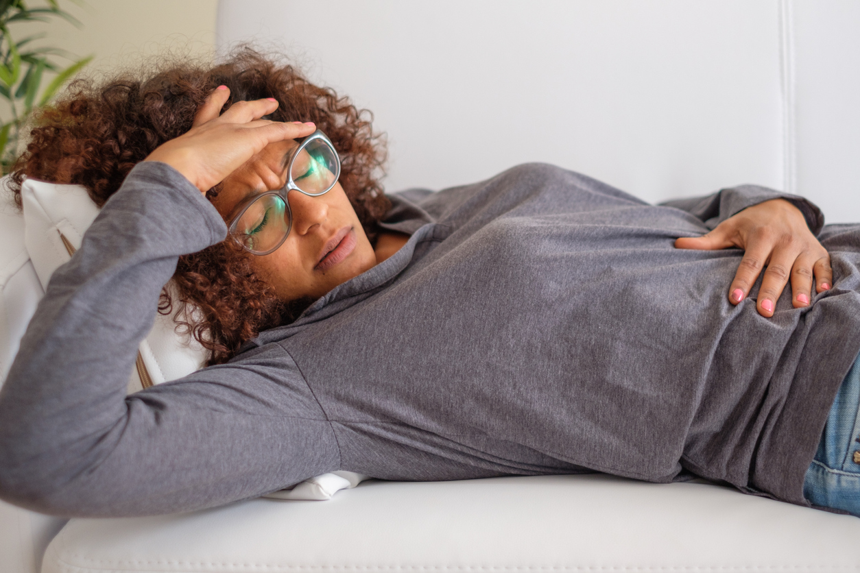 Woman feeling pain to the stomach lying on sofa, highlight the truth behind premenstrual syndrome, PMS.