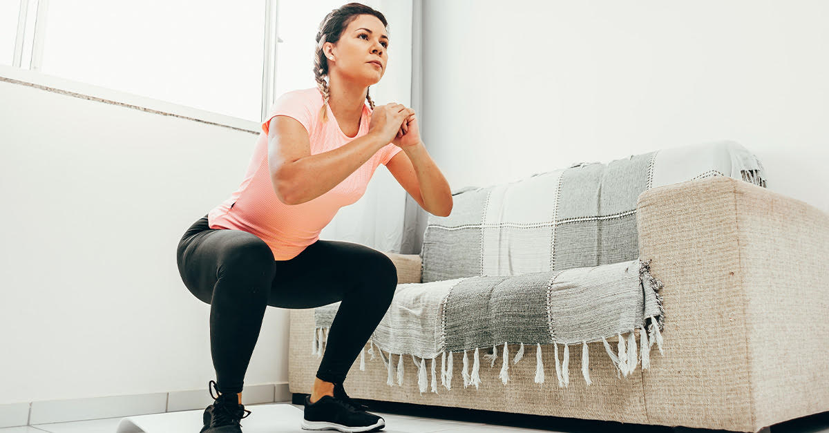 Young woman doing squats in living room